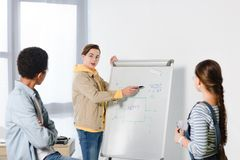 Teen boy presenting something on flipchart to multicultural friends. At home royalty free stock photos