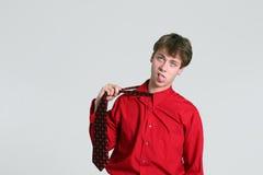 Teen boy pulling on necktie Stock Photo