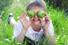 Teen boy with pyramid of green apples lying on Stock Photo