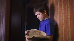 Teen boy reading book education is wall indoor stock footage