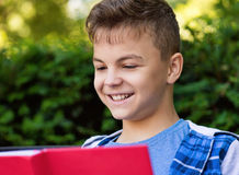Teen boy reading book. Outdoor portrait of happy teen boy 12-14 year old, reading book at park Stock Photos