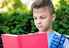 Teen boy reading book. Outdoor portrait of happy teen boy 12-14 year old, reading book at park Stock Photography