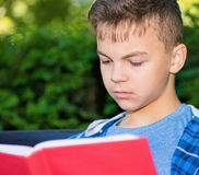 Teen boy reading book. Outdoor portrait of teen boy 12-14 year old, reading book at park Stock Images