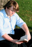 Teen Boy Reading Outdoors. Teenage boy sitting on the ground by a tree, reading a paperback book royalty free stock photo