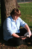 Teen Boy Reading In Park. Teenage boy sitting on the ground against a tree in a park, reading a paperback book stock photo