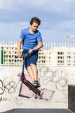 Teen boy rides his scooter at the skate park Royalty Free Stock Photos