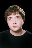 Teen boy rolling eyes. Young guy eyeroll over a black background Royalty Free Stock Photography