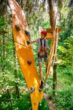 Teen boy on a ropes course in a treetop adventure park passing hanging rope obstacle. Teenager boy wearing safety harness passing rope bridge obstacle at a ropes royalty free stock images