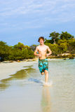 Teen boy is running along the tropical beach Stock Image