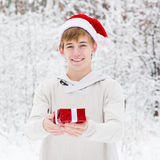 Teen boy with santa hat and red gift box standing in winter forest Stock Image