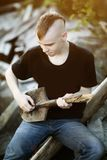 Teen boy with a shovel as a guitar in his hands. Difficult awkwa Stock Photography