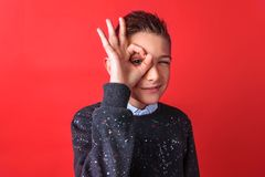 Teen boy showing OK sign isolated on red background stock images