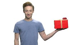 Teen boy showing red gift box. Portrait of handsome teenage boy offering wrapped gift box on white background. Give presents for your loved ones stock video footage