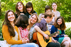 Teen boy singin by guitar for girls Royalty Free Stock Image