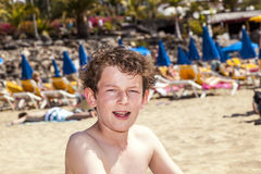 Teen boy sits at the beach Stock Images