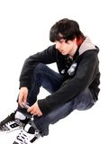 Teen boy sitting. A teenage boy is sitting on the floor in the studio with his game boy on Stock Photos