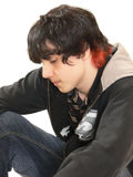 Teen boy sitting. A teenage boy is sitting on the floor in the studio with his game boy on Royalty Free Stock Image