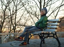 Teen boy sitting on a bench in a city park stock photography