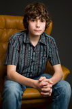Teen boy sitting in a chair. Teenage boy sitting in a chair looking at the camera Royalty Free Stock Image