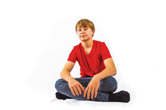 Teen boy sitting crossed-legged in the studio Stock Images