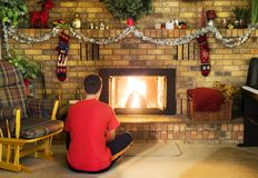 Teen boy sitting in front of roaring fire in brick fireplace dec Royalty Free Stock Photo