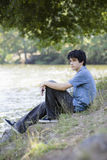 Teen Boy Sitting By Lake Royalty Free Stock Images