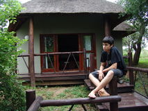 Teen boy sitting outside. Pensive teenage boy sitting on the post of a wooden walkway leading up to a small home behind him Royalty Free Stock Image