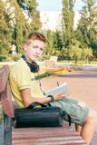 Teen boy is sitting and writing on the bench.  Stock Photo