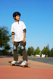 Teen Boy on Skateboard. Teenage boy riding a skateboard on the sidewalk of a parking lot on a sunny day with blue sky and trees in the background Stock Photos