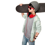 Teen boy with skateboard. On the shoulder isolated on white background, stylish guy wearing sunglasses and hat, listening music from earphone, modern life of Stock Image