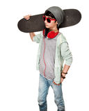 Teen boy with skateboard. On the shoulder, isolated on white background, stylish guy wearing sunglasses and hat, listening music from earphone, modern life of Stock Photography