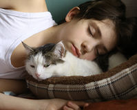 Teen boy sleep with cat stock photo