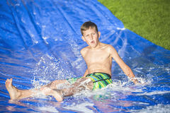 Teen boy sliding down a slip and slide outdoors Stock Photo