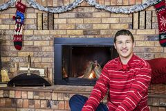 Teen boy smiling sitting in front of cozy fireplace decorated fo. R Christmas. Cozy holiday scene with stockings and tinsel hung Royalty Free Stock Image