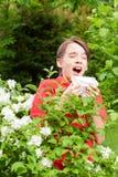 Teen boy sneezing in a spring garden seasonal infection concept royalty free stock image