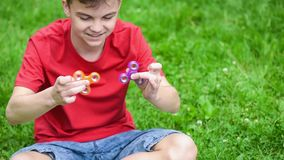 Teen boy with spinner in park stock footage