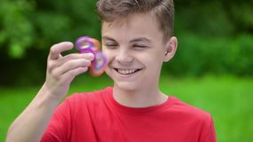 Teen boy with spinner in park stock video