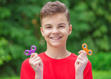 Teen boy with spinner toy in park. Young teen boy holding popular fidget spinner toy - outdoors portrait. Happy smiling child playing with a orange Spinner in Royalty Free Stock Photography