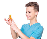 Teen boy with spinner on white. Young teen boy holding popular fidget spinner toy - close up portrait. Happy smiling child playing with Spinner, isolated on Stock Photo