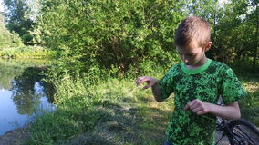 Teen boy standing on the shore of the old overgrown pond stock video footage