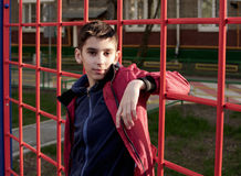 Teen boy stands near the red playground stairs Royalty Free Stock Photos