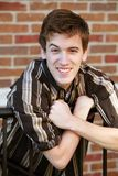 Teen boy in striped shirt. Handsome teen boy by brick wall smiling Royalty Free Stock Photo