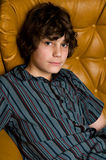 Teen boy in studio. Teen boy sitting in a chair looking at the camera Stock Photo