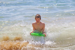 Teen boy surfing in the waves. Cute boy surfing in the waves stock photos