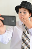 Teen boy with surprise looks at  mobile phone Royalty Free Stock Image