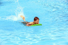 Teen boy swimming in a pool with a boogie board Stock Photography