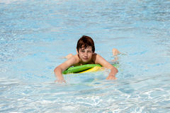 Teen boy swimming in a pool with a boogie board. Smiling teen boy swimming in a pool with a boogie board Stock Photo