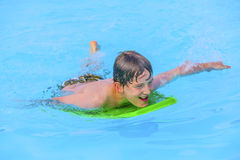 Teen boy swimming in a pool with a boogie board. Smiling teen boy swimming in a pool with a boogie board Royalty Free Stock Images