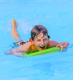 Teen boy swimming in the pool. Cute teen boy swimming in the pool Royalty Free Stock Images