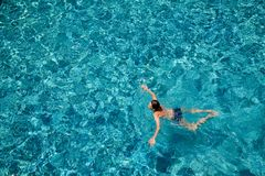 Teen boy swimming in a pool outdoors royalty free stock photo